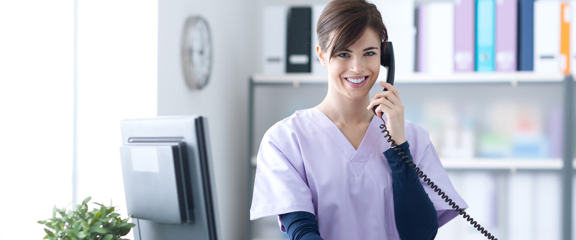 Receptionist answering a phone call at dental office