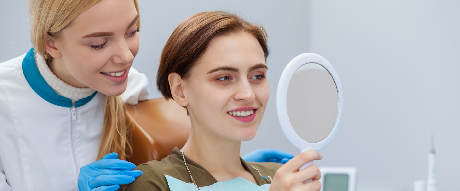 Female patient at dental clinic checking her teeth using a hand mirror