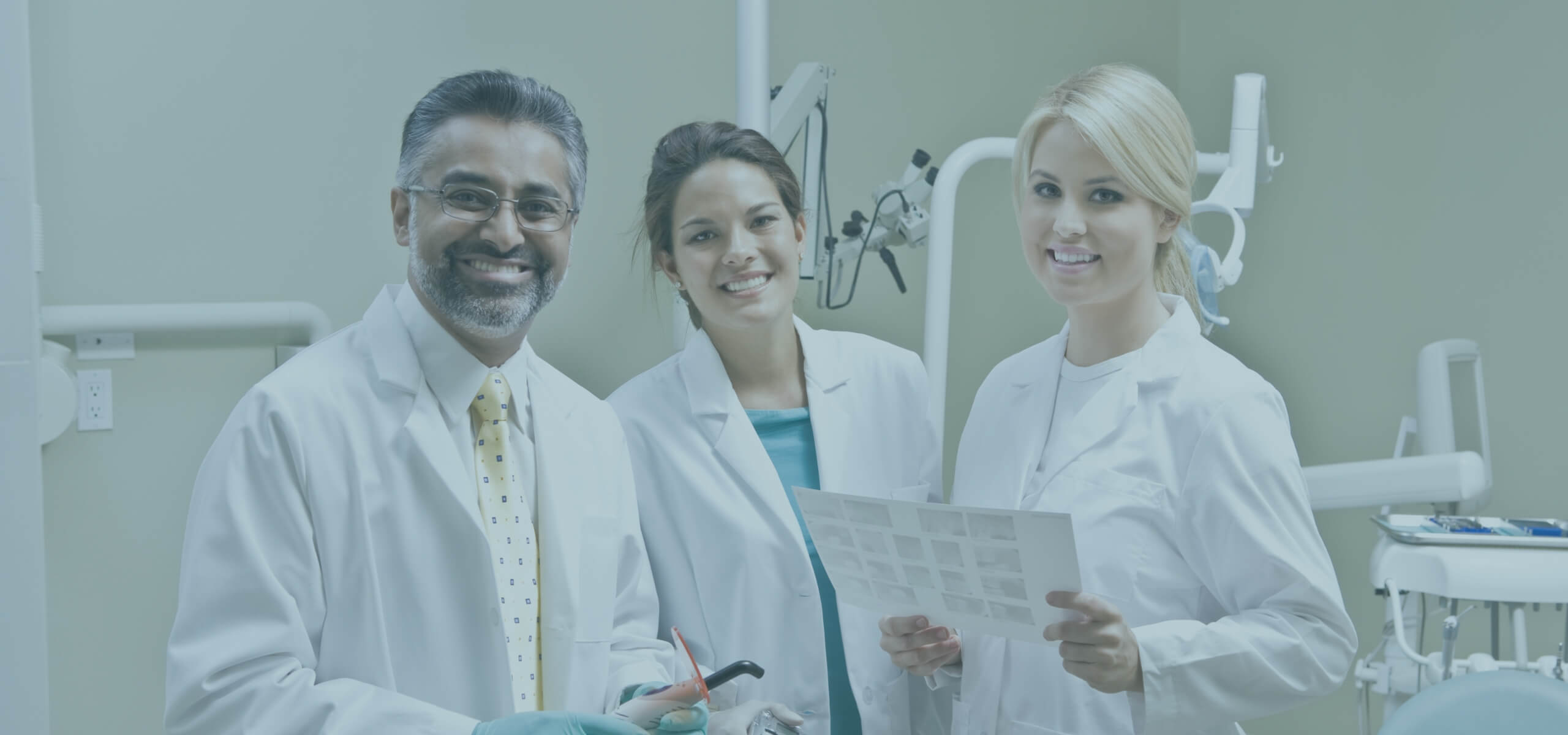 Dentist and two female dental assistants smiling at the camera