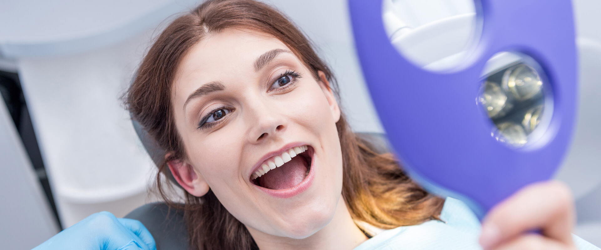 Smiling female patient checking her new smile using a hand mirror