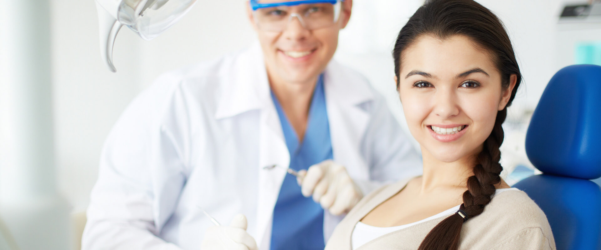 Female patient smiling at the camera seated on dental chair with dentist in the background